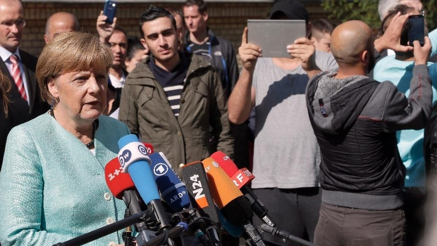 FILE - In this Sept. 10, 2015, file photo people take pictures as German Chancellor Angela Merkel, left, speaks during a statement as part of a visit at a registration center for migrants and refugees in Berlin, Germany. Germany marks a quarter-century as a reunited nation on Saturday, Oct. 3, 2015, with two leaders from the formerly communist east heading a country that increasingly asserts itself as Europe's political heavyweight, and now faces a new challenge in a refugee influx that will demand deep reserves of resourcefulness and patience. (AP Photo/Michael Sohn, File)