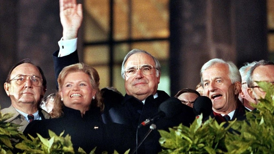 FILE - In this Oct. 3, 1990 photo from left: German Foreign Minister Hans-Dietrich Genscher, the chancellor's wife Hannelore Kohl, German Chancellor Helmut Kohl and German president Richard von Weizsaecker stand in front of the German Reichtags building during re-unification celebrations in Berlin. Germany marks a quarter-century as a reunited nation on Saturday, Oct. 3, 2015, with two leaders from the formerly communist east heading a country that increasingly asserts itself as Europe's political heavyweight, and now faces a new challenge in a refugee influx that will demand deep reserves of resourcefulness and patience. (Wolfgang Kumm/dpa via AP, File)