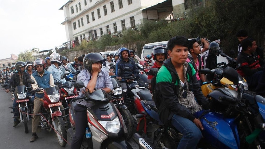 FILE - In this Sept. 28, 2015, file photo, Nepalese motorists wait for their turn to fill fuel on their motorbikes at a fuel pump run by the Nepalese army in Kathmandu, Nepal. Long lines of vehicles snaked around gasoline stations in Kathmandu amid fuel restrictions imposed by the government. The shortages come after Indian trucks carrying goods stopped at the border. Nepal obtains most of its fuel and other vital supplies from India. Many Nepalis believe that India has been retaliating against their government since Sept. 20, 2015, when it approved a new constitution seen by New Delhi as discriminatory to an ethnic Indian community - the Madhesi - living in Nepal's border districts. (AP Photo/Niranjan Shrestha, File)