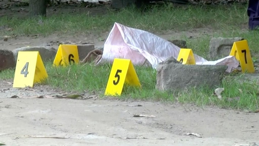 In this image made from video, evidence markers are used as investigators work at the site where Japanese national Kunio Hoshi was shot and killed in Mahiganj village in Rangpur district, Bangladesh, Saturday, Oct. 3, 2015. Masked assailants riding a motorbike shot and killed a Japanese man in northern Bangladesh on Saturday, police said, the second foreigner in a week to be gunned down in the South Asian country. (APTN via AP)