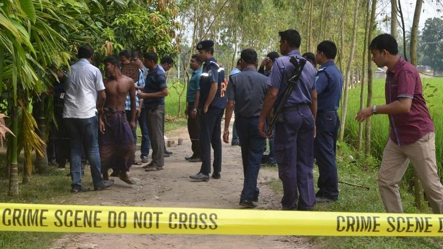 Bangladeshi security officers stand by the site where a Japanese Kunio Hoshi was killed at Mahiganj village in Rangpur district, 300 kilometers (185 miles) north of Dhaka, Bangladesh, Saturday, Oct. 3, 2015. Masked assailants riding a motorbike shot and killed the Japanese man in northern Bangladesh on Saturday, police said, the second foreigner in a week to be gunned down in the South Asian country. Hoshi had started a farm in Rangpur, about 300 kilometers (185 miles) north of Dhaka, to produce grass. (AP Photo/Ripon Islam)
