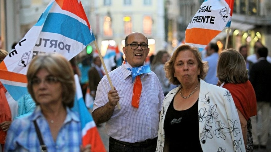 Supporters of the ruling center-right government coalition take part in an election campaign march in Lisbon, Portugal, Friday, Oct. 2, 2015. Portugal goes to the polls to elect a new government on Sunday. (AP Photo/Armando Franca)