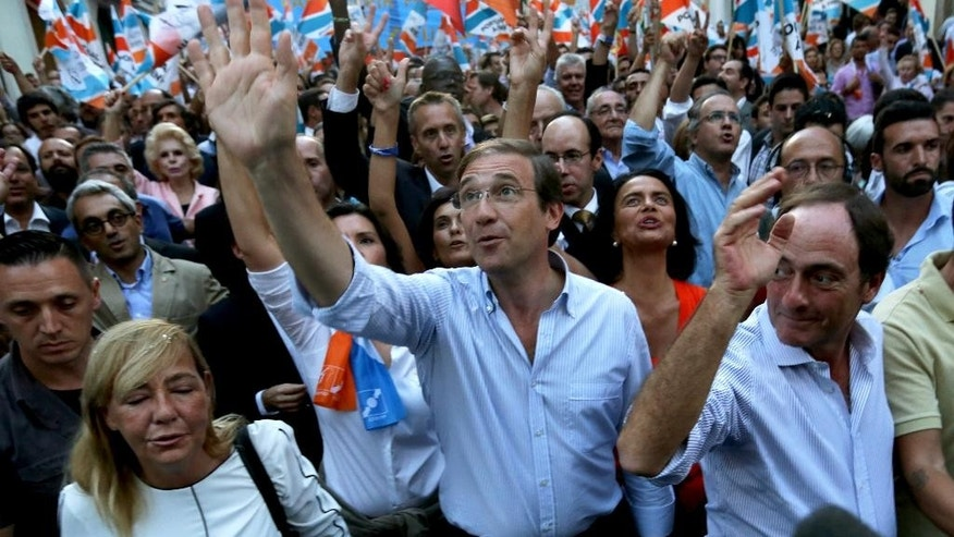 Portuguese Prime Minister Pedro Passos Coelho, center, and Deputy Prime Minister Paulo Portas, right, wave during an election campaign march in Lisbon, Portugal, Friday, Oct. 2, 2015. Portugal goes to the polls to elect a new government on Sunday. (AP Photo/Armando Franca)