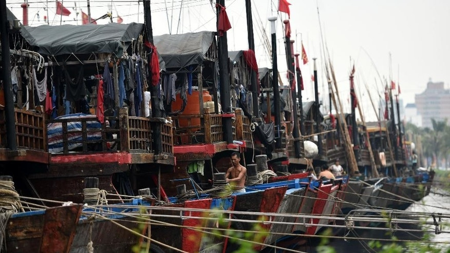 In this Oct. 3, 2015 photo provided by China's Xinhua News Agency, ships berth at Xingang harbor in Haikou, capital of south China's Hainan Province.  Tens of thousands of people have been evacuated from coastal areas of southern China, with a strong typhoon that was moving toward the mainland on Sunday, Oct. 4,  already bringing powerful winds and heavy rain to the region.  Typhoon Mujigae was heading gradually toward the Leizhou Peninsula in Guangdong province, just north of the resort island of Hainan, according to the National Meteorological Center. (Zhao Yingquan/Xinhua News Agency via AP) NO SALES
