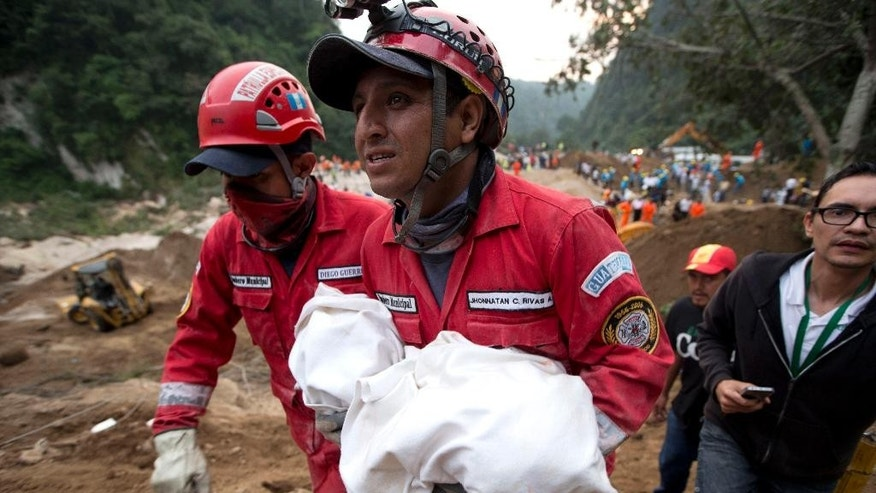 A fireman carries the body of a child recovered from the site of a landslide in Cambray, a neighborhood in the suburb of Santa Catarina Pinula, about 10 miles east of Guatemala City, Friday, Oct. 2, 2015. The hill that towers over Cambray collapsed late Thursday after heavy rains, burying several houses with dirt, mud and rocks. Family members have reported 100 people missing, but the number could be as high as 600 based on at least 100 homes in the area of the slide, said Alejandro Maldonado, executive secretary of Conred, the country's emergency disaster agency. (AP Photo/Moises Castillo)