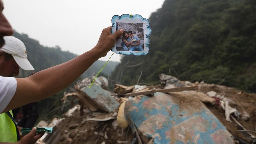 A resident holds up a photo of his neighbors to show rescue workers during a search for survivors at the site of a landslide in Cambray, a neighborhood in the suburb of Santa Catarina Pinula, about 10 miles east of Guatemala City, Friday, Oct. 2, 2015. The hill that towers over Cambray collapsed late Thursday after heavy rains, burying several houses with dirt, mud and rocks. Family members have reported 100 people missing, but the number could be as high as 600 based on at least 100 homes in the area of the slide, said Alejandro Maldonado, executive secretary of Conred, the country's emergency disaster agency. (AP Photo/Moises Castillo)