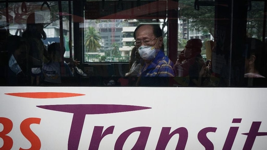 A man wears a face mask on a public bus, Saturday, Oct. 3, 2015, in Singapore.  The haze is caused by the burning of forests in Indonesia's Sumatra and Borneo islands. (AP Photo/Wong Maye-E)