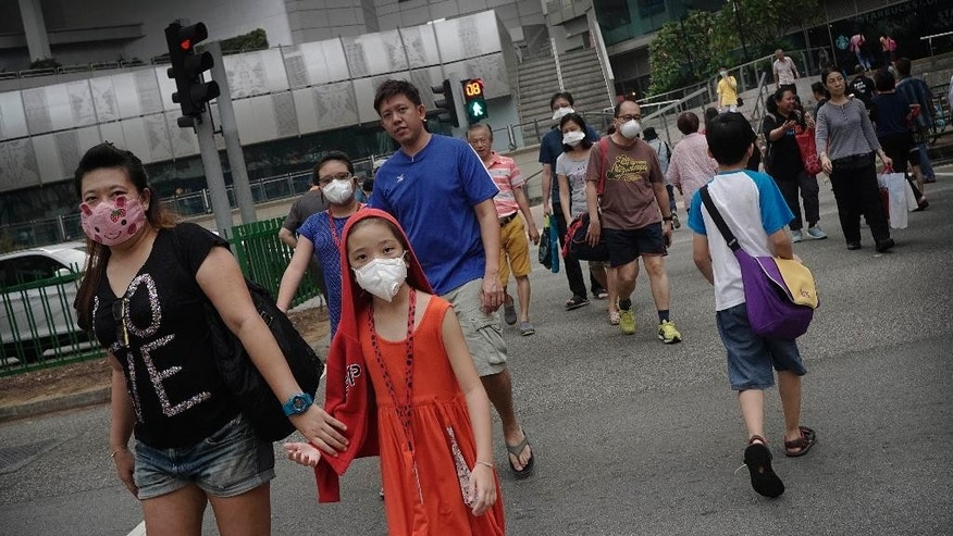 People wear face masks to protect themselves from the haze, as they cross the street at a local mall, Saturday, Oct. 3, 2015, in Singapore. The haze is caused by the burning of forests in Indonesia's Sumatra and Borneo islands.  (AP Photo/Wong Maye-E)