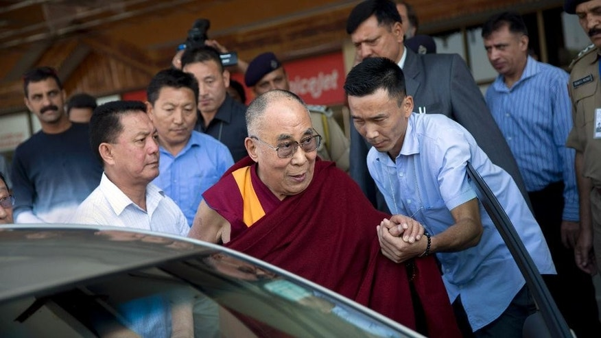 Exile Tibetan spiritual leader the Dalai Lama is helped into a car as he exits the Kangra Airport in Dharmsala, India, Saturday, Oct. 3, 2015. The Dalai Lama has assured his followers that he is in excellent health upon his return to the Tibetan government-in-exile's headquarters in northern India. The Tibetan leader's assurances came days after doctors at the Mayo Clinic instructed him to rest. He later canceled his October appearances in the United States. (AP Photo /Tsering Topgyal)