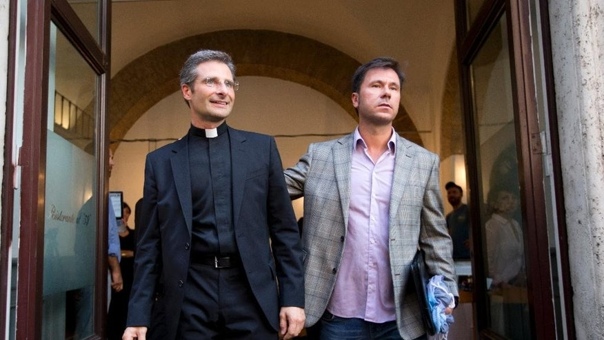 Monsignor Krzysztof Charamsa, left, and his boyfriend Eduard, surname not given, pose for a photo after a press conference in Rome Saturday. (AP Photo/Alessandra Tarantino)