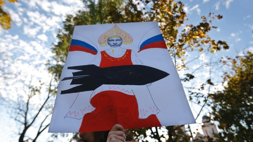 A demonstrator holds a placard depicting Russia's President Vladimir Putin during opposition rally against the deployment of Russian military bases in Belarus, in Minsk, Sunday, Oct. 4, 2015. (AP Photo/Sergei Grits)