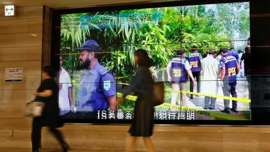People walk past a screen showing TV news reports of Saturday's militant attack on a Japanese in Bangladesh, in Tokyo, Sunday, Oct. 4, 2015.  Japanese officials said Sunday that they were investigating the fatal shooting of a Japanese citizen in Bangladesh as a possible terrorist attack after the Islamic State group claimed responsibility for the killing. (AP Photo/Shizuo Kambayashi)