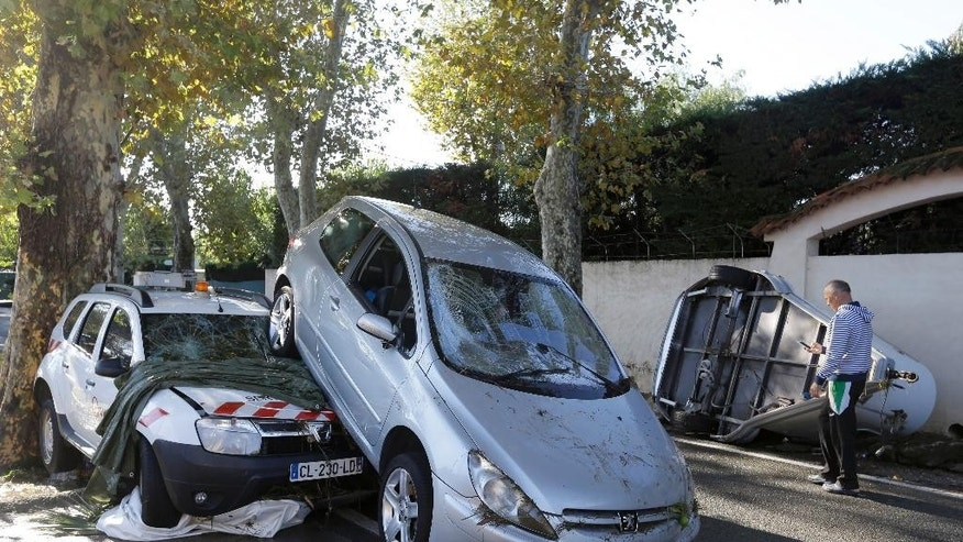 A man walks past damaged cars in Biot, near Cannes, southeastern France, Sunday Oct.4, 2015. Sudden heavy rains around the French Riviera have killed at least 10 people, including some trapped in cars, a campsite and a retirement home, and left six missing. Car and train traffic was disrupted along the Mediterranean coast. (AP Photo/Lionel Cironneau)