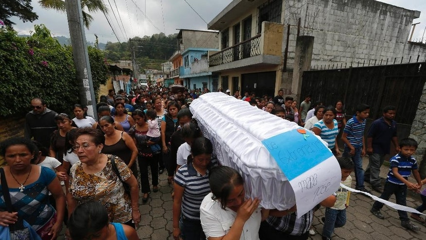 "People carry the white coffin of ten-year-old Maria Jose Estrada, and her uncle Amilcar Estrada, back, who both died in a mudslide, to the Santa Catarina Pinula cemetery on the outskirts of Guatemala City, Sunday, Oct. 4, 2015. The sign on the white coffin reads in Spanish ""We miss you Maria Jose."" Rescue workers recovered more bodies Saturday after a hillside collapsed on homes late Thursday, while more are feared still buried in the rubble. (AP Photo/Moises Castillo)"