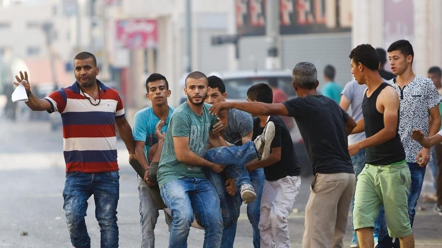 Palestinians carry an injured man during an Israeli military raid in the West Bank city of Jenin, Sunday, Oct. 4, 2015. Israeli troops shot and wounded at least 18 Palestinians in violence during an arrest raid in the Jenin refugee camp, a Palestinian hospital director said. (AP Photo/Majdi Mohammed)