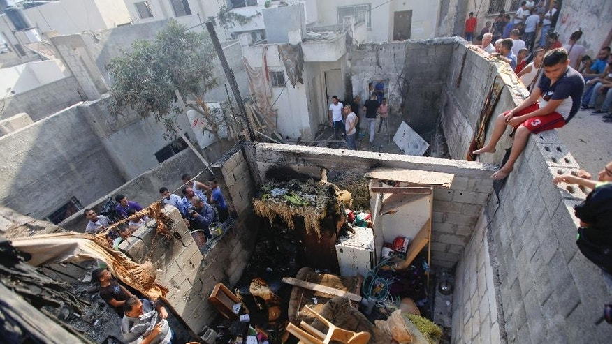 Palestinians inspect the house of Qais al-Saadi, a member of the Hamas' al-Qassam Brigades, after an Israeli military raid in the West Bank city of Jenin, Sunday, Oct. 4, 2015. Israeli troops shot and wounded at least 18 Palestinians in violence during an arrest raid in the Jenin refugee camp, a Palestinian hospital director said. (AP Photo/Majdi Mohammed)