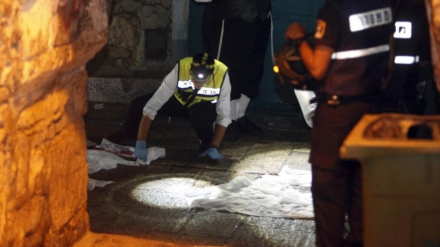 Israeli forensic inspect the scene of an attack in Jerusalem's Old City, Saturday, Oct. 3, 2015. A Palestinian fatally stabbed two Israelis as they walked in Jerusalem's Old City and seriously injured a toddler and a woman, before he was shot and killed by an officer on duty, police said Saturday in the latest in a series of Palestinian attacks. (AP Photo/Mahmoud Illean)