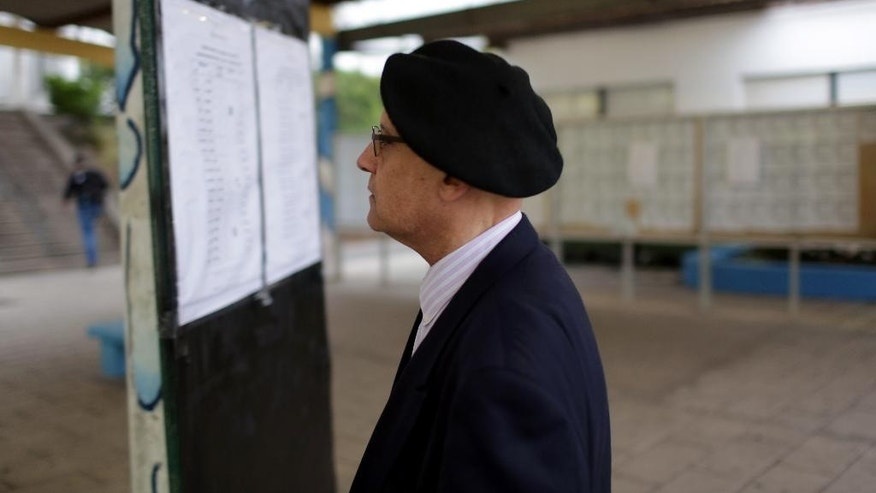 A man looks for his voter registration number to vote in Portugal's general elections at a polling station in Massama, outside Lisbon, Sunday, Oct. 4 2015. The last polls ahead of Sunday's election showed the center-right ruling coalition roughly level  with the center-left Socialist Party, the main opposition. (AP Photo/Armando Franca)