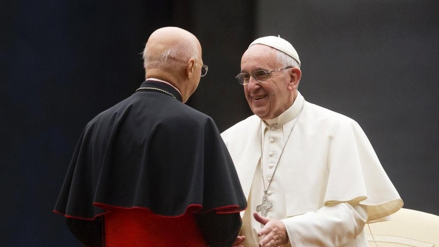 Pope Francis greets Italian Episcopal conference (CEI) president Cardinal Angelo Bagnasco, left, during a vigil ahead of the opening of the Synod of bishops, in St. Peter's Square at the Vatican, Saturday, Oct. 3, 2015. (AP Photo/Riccardo De Luca)