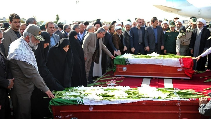 Iranian officials pray as they touch the coffin of a dead hajj pilgrim who was killed in a deadly stampede in Mina near Mecca in Saudi Arabia on September 24, at Mehrabad airport in Tehran, Iran, Saturday, Oct. 3, 2015. The first plane carrying bodies of Iranian pilgrims killed in the hajj stampede in Saudi Arabia arrived in Tehran Saturday, nine days after the disaster that escalated tensions between the two regional rivals. President Hassan Rouhani and other senior officials were at the airport for the arrival of the plane, which carried 104 bodies. (AP Photo/Ebrahim Noroozi)