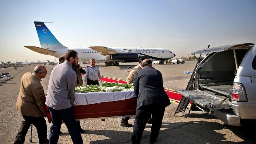 Iranian men load the coffin of a dead hajj pilgrim who was killed in a deadly stampede in Mina near Mecca in Saudi Arabia on September 24, into a car at Mehrabad airport in Tehran, Iran, Saturday, Oct. 3, 2015. The first plane carrying bodies of Iranian pilgrims killed in the hajj stampede in Saudi Arabia arrived in Tehran Saturday, nine days after the disaster that escalated tensions between the two regional rivals. President Hassan Rouhani and other senior officials were at the airport for the arrival of the plane, which carried 104 bodies. (AP Photo/Ebrahim Noroozi)