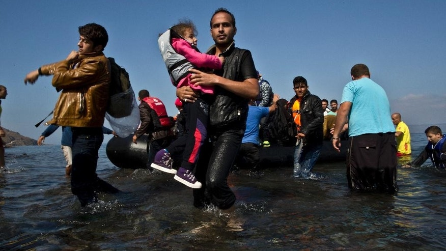 "A Syrian refugee man carrying his daughter rushes to the beach as he arrives on a dinghy from the Turkish coast to the northeastern Greek island of Lesbos, Sunday, Oct. 4 , 2015. The U.N. refugee agency is reporting a ""noticeable drop"" this week in arrivals of refugees by sea into Greece - as the total figure for the year nears the 400,000 mark. Overall, the UNHCR estimates 396,500 people have entered Greece via the Mediterranean this year with seventy percent of them are from war-torn Syria. (AP Photo/Muhammed Muheisen)"