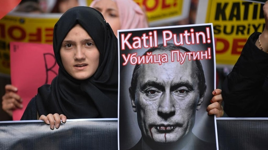 A demonstrator holds a picture depicting Russian President Vladimir Putin during a protest against Russian military operations in Syria, in Istanbul, Turkey, Saturday, Oct. 3, 2015. The picture reads both in Turkish and Russian: 'Murderer Putin'. In ramping up its military involvement in Syria's civil war, Russia appears to be betting that the West, horrified by Islamic State's atrocities, may be willing to tolerate Syrian President Bashar Assad for a while, perhaps as part of a transition. (AP Photo)