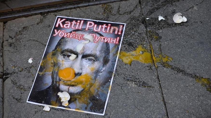 A picture depicting Russian President Vladimir Putin is splattered with eggs during a protest against Russian military operations in Syria, in Istanbul, Turkey, Saturday, Oct. 3, 2015. The picture reads both in Turkish and Russian: 'Murderer Putin'. In ramping up its military involvement in Syria's civil war, Russia appears to be betting that the West, horrified by Islamic State's atrocities, may be willing to tolerate Syrian President Bashar Assad for a while, perhaps as part of a transition. (AP Photo)