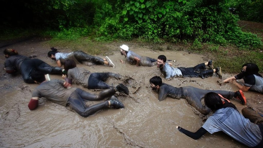 "In this Sept. 14, 2015 photo, students from Suan Sunandha Rajabhat University crawl on their stomachs through muddy jungle paths as part of an exercise designed to ""break down their ego (and) humiliate them"" at a military boot camp ordered as punishment for a hazing incident in Nakhon Nayok province, Thailand. In military-ruled Thailand there is a new method for teaching discipline known as ""attitude adjustment,"" which until now has been used to silence government critics. But there are signs that the mentality of military rule is creeping into civilian issues - like college discipline. (AP Photo/Sakchai Lalit)"