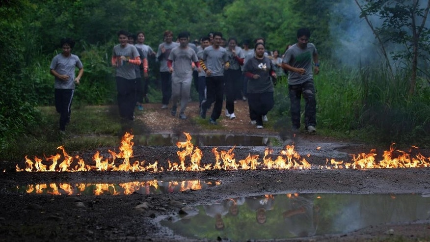 "In this Sept. 14, 2015 photo, film students from Suan Sunandha Rajabhat University run through a jungle trail laid with a barricade of fire as part of a mandatory three-day boot camp at a military facility that was ordered as punishment for a hazing incident in Nakhon Nayok province, Thailand. In military-ruled Thailand there is a new method for teaching discipline known as ""attitude adjustment,"" which until now has been used to silence government critics. But there are signs that the mentality of military rule is creeping into civilian issues - like college discipline. (AP Photo/Sakchai Lalit)"