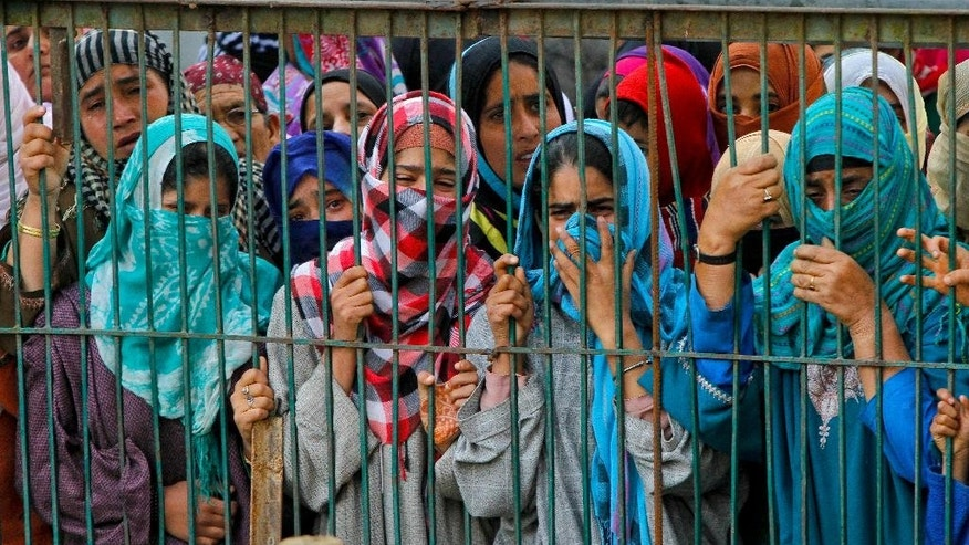 Kashmiri Muslim women wail as they watch the funeral procession of suspected rebels, at Barhama, 40 kilometers (25 miles) south of Srinagar, Indian controlled Kashmir, Monday, Oct. 5, 2015. At least four Indian army soldiers and three suspected rebels were killed in three separated gun battles in Indian-controlled Kashmir, police said on Monday. (AP Photo/Mukhtar Khan)