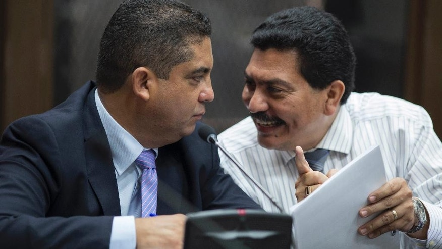 """Juan Carlos Monzon Rojas, left, the personal secretary of former Vice President Roxana Baldetti, listens to his lawyer Francisco Garcia Gudiel during a court hearing after he turned himself in to authorities in Guatemala City, Monday, Oct. 5, 2015. Monzon is accused by authorities of being the head of a corruption ring, known as """"La Linea,"""" in which businesses allegedly paid kickbacks to government officials in exchange for lower import duties, which is believed to have bilked the government of millions of dollars. The corruption scandal has rocked the Guatemalan government and so far has caused the resignation of former President Otto Perez Molina and Baldetti, both jailed and facing charges for allegedly receiving the illegal payments. (AP Photo/Luis Soto)"""