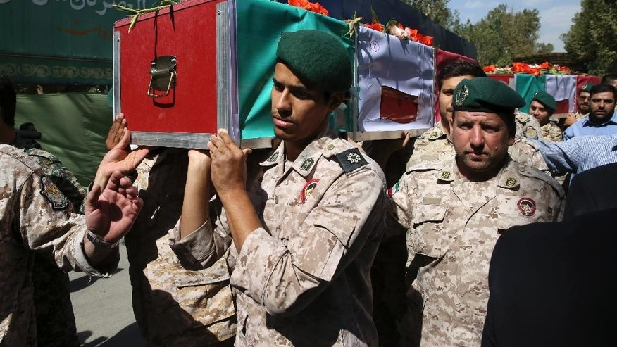 Members of Iran's Revolutionary Guard carry the flag draped coffin of a pilgrim who was killed during the hajj pilgrimage in Saudi Arabia last month as thousands of mourners attend funeral services for some of the victims, in Tehran, Iran, Sunday, Oct. 4, 2015. Iran has blamed Saudi authorities for the disaster, which heightened tensions between the two regional rivals. Saudi authorities say 769 pilgrims died in the stampede near Mecca in the worst disaster to strike the annual pilgrimage in a quarter-century. Iran appears to have lost the largest number of pilgrims, with at least 464 dead. (AP Photo/Vahid Salemi)