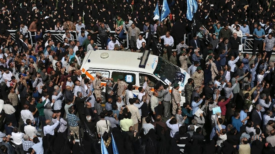 An ambulance carries the body of a pilgrim who was killed in a stampede during the hajj pilgrimage in Saudi Arabia last month as thousands of mourners attend funeral services for some of the victims, in Tehran, Iran, Sunday, Oct. 4, 2015. Iran has blamed Saudi authorities for the disaster, which heightened tensions between the two regional rivals. Saudi authorities say 769 pilgrims died in the stampede near Mecca in the worst disaster to strike the annual pilgrimage in a quarter-century. Iran appears to have lost the largest number of pilgrims, with 464 dead. (AP Photo/Vahid Salemi)