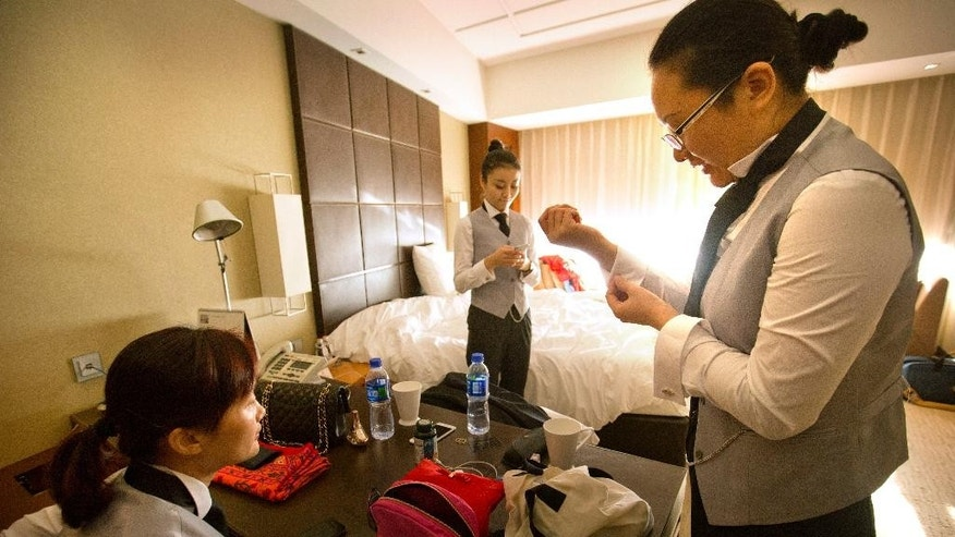 In this Friday, Sept. 25, 2015 photo, Chinese butler school graduate Zhang Dejing, right, adjusts her cuffs while preparing for a day of butler duties at a conference with fellow graduates Ma Xueling, left, and Duan Xiangyin, center, in their hotel room in Beijing. A butler is a new must-have for some of China's super-rich. Prompted by the popularity in China of the British TV series 'Downtown Abbey' and a fondness for anything that looks expensive and feels European, some of China's very wealthy want a uniformed employee with white gloves, impeccably trained, who can anticipate your every need at home. (AP Photo/Mark Schiefelbein)