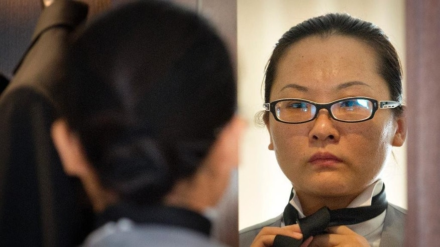 In this Friday, Sept. 25, 2015 photo, Chinese butler school graduate Zhang Dejing ties her necktie while looking in a mirror as she prepares in her hotel room for a day of butler duties at a conference in Beijing. A butler is a new must-have for some of China's super-rich. Prompted by the popularity in China of the British TV series 'Downtown Abbey' and a fondness for anything that looks expensive and feels European, some of China's very wealthy want a uniformed employee with white gloves, impeccably trained, who can anticipate your every need at home. (AP Photo/Mark Schiefelbein)
