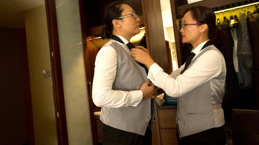 In this Friday, Sept. 25, 2015 photo, Chinese butler school graduate Ma Xueling, right, helps fellow graduate Zhang Dejing adjust her necktie as the two prepare for a day of butler duties at a conference in their hotel room in Beijing. A butler is a new must-have for some of China's super-rich. Prompted by the popularity in China of the British TV series 'Downtown Abbey' and a fondness for anything that looks expensive and feels European, some of China's very wealthy want a uniformed employee with white gloves, impeccably trained, who can anticipate your every need at home. (AP Photo/Mark Schiefelbein)
