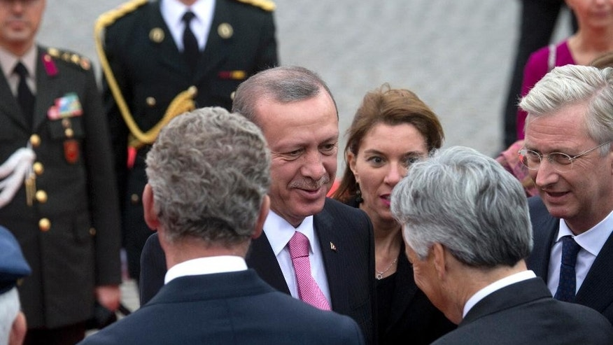 Turkish President Recep Tayyip Erdogan, center, greets Belgium's King Philippe, right, Belgian Foreign Minister Didier Reynders, second right, and Belgian Defense Minister Pieter De Crem, fourth right, as he arrives at the Royal Palace in Brussels on Monday, Oct. 5, 2015. Erdogan is on a two-day visit to meet Belgian and EU officials. (AP Photo/Virginia Mayo)