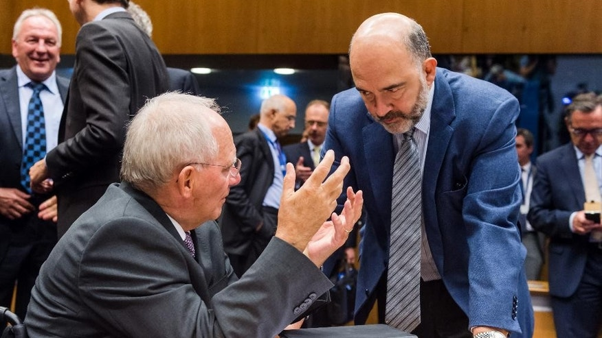 Germany's Finance Minister Wolfgang Schauble, left, talks with European Commissioner for Economic and Financial Affairs Pierre Moscovici during a meeting of eurogroup finance ministers at the EU Council building in Luxembourg, Monday, Oct. 5, 2015. (AP Photo/Geert Vanden Wijngaert)