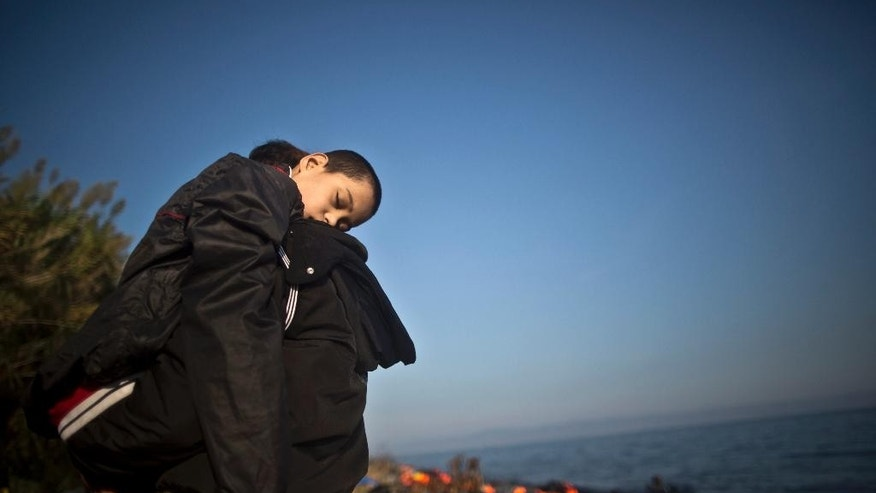 An Afghan refugee child lies on his father's shoulder shortly after arriving on a dinghy from the Turkish coast to the northeastern Greek island of Lesbos, Monday, Oct. 5, 2015. (AP Photo/Muhammed Muheisen)