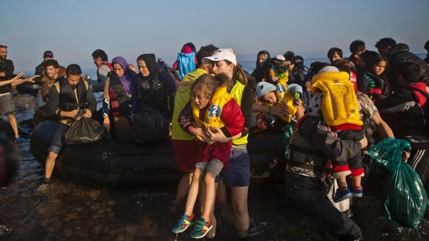 An Afghan refugee girl is helped by a volunteer as she and other migrants arrive on a dinghy from the Turkish coast to the northeastern Greek island of Lesbos, Monday, Oct. 5, 2015. (AP Photo/Muhammed Muheisen)