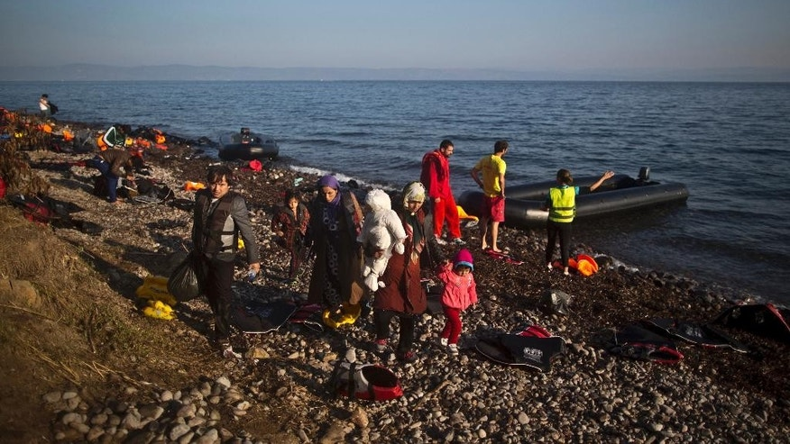 Refugees walk toward the main road shortly after arriving on a dinghy from the Turkish coast to the northeastern Greek island of Lesbos, Monday, Oct. 5 , 2015. (AP Photo/Muhammed Muheisen)