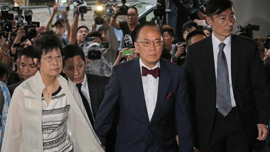 Donald Tsang, center, former leader of Hong Kong and his wife Selina arrive at a magistrates' court in Hong Kong Monday, Oct. 5, 2015. Tsang faces misconduct charges over a luxury apartment rental in mainland China, authorities said Monday, setting the stage for the city's most high-profile corruption trial in recent memory. (AP Photo/Vincent Yu)
