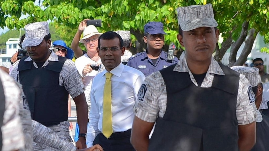 """FILE - In this Wednesday, Sept. 9, 2015 file photo, Maldives former president Mohamed Nasheed, center, escorted by policemen returns after appearing at the High Court in Male, Maldives. Human rights lawyer Amal Clooney says the imprisonment of former Maldives President Mohamed Nasheed symbolizes a turn toward autocracy and extremism by a Muslim nation with the world's highest per-capita level of recruitment to the Islamic State group. Clooney is part of an international legal team that vowed Monday, Oct. 5, 2015 to apply """"relentless"""" pressure on the Maldives government, seeking international sanctions and travel bans on senior officials until Nasheed is freed. (AP Photo/ Mohamed Sharuhaan, File)"""