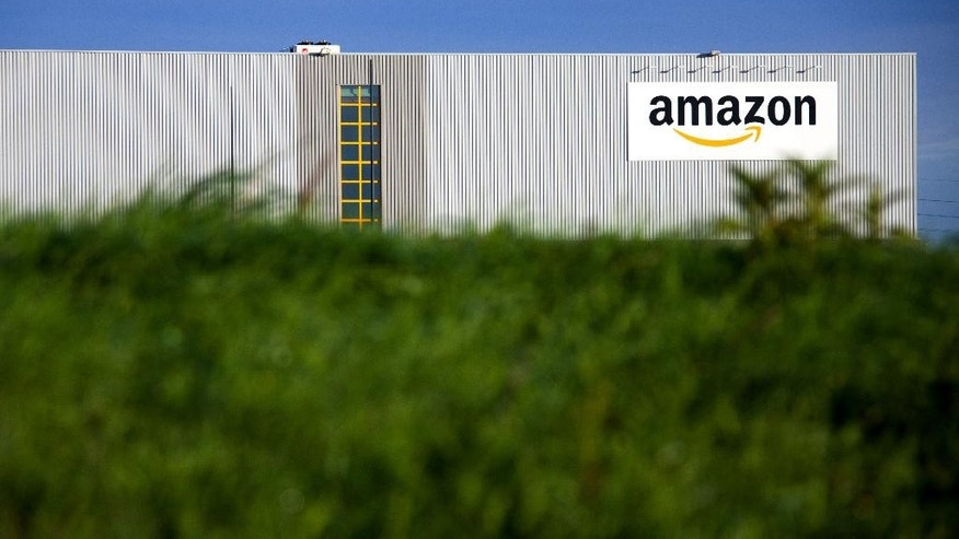 This Sept.19, 2013 photo shows the logistics center of online merchant Amazon in Lauwin-Planque, northern France. The Organization for Economic Cooperation and Development released a plan Monday, Oct.5, 2015 to end tax shelters and require companies to pay taxes in the countries where they earn profits, among other measures. Google, Facebook, Starbucks and Amazon are among many companies criticized for shifting profits to low-tax jurisdictions. (AP Photo/Michel Spingler)