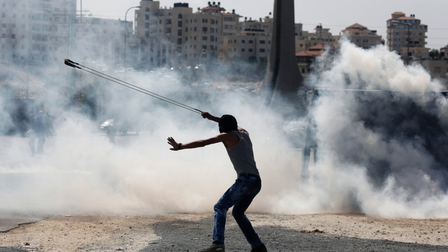 Oct. 5, 2015- A Palestinian demonstrator uses a slingshot during clashes following a demonstration in the West Bank city of Ramallah. 2 Palestinian youths were killed in clashes with Israeli soldiers in the West Bank as fears spread of a further escalation in violence that has already killed several Israeli civilians and wounded hundreds of Palestinian protesters over the past days.