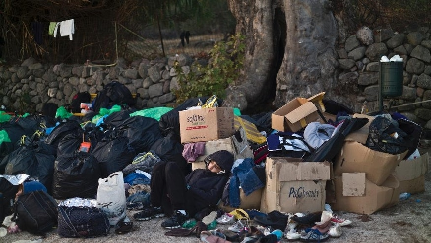 A Syrian refugee boy sleeps on a roadside amid donated clothes and shoes after he and his family arrived on a dinghy from the Turkish coast to the northeastern Greek island of Lesbos, Monday, Oct. 5 , 2015. (AP Photo/Muhammed Muheisen)