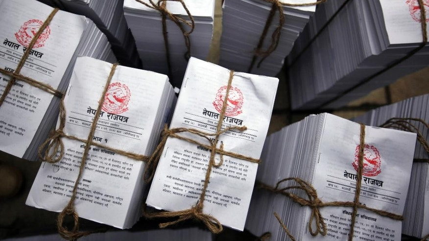 FILE - In this Sunday, Sept. 20, 2015 file photo, copies of the newly adopted constitution lie bundled together for distribution to lawmakers at the constituent assembly hall in Kathmandu, Nepal. Leaders of Nepal's three main political parties discussed formation of a new government on Monday following the adoption of a new constitution last month. (AP Photo/Niranjan Shrestha, File)