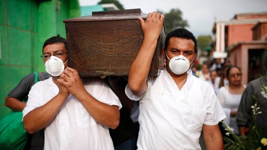 Men with their mouths covered wih surgical masks carry the coffin of a victim of the Cambray neighborhood mudslide, to the Santa Catarina Pinula cemetery on the outskirts of Guatemala City, Sunday, Oct. 4, 2015. Hope faded Sunday for finding any survivors of a mudslide that killed at least 87 people as authorities said that hundreds more may still be missing. (AP Photo/Luis Soto)