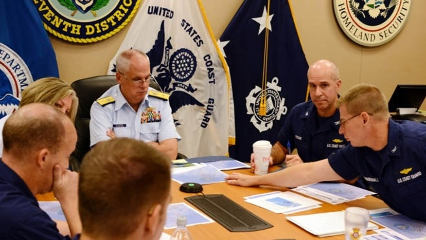 Rear Adm. Scott Buschman, commander of the Coast Guard 7th District, receives an update brief for the missing cargo ship El Faro at the Coast Guard 7th District in Miami, Saturday, Oct. 3, 2015. The ship was heading from Jacksonville, Fla, to San Juan, Puerto Rico when it was battered by waves. (Petty Officer 2nd Class Jon-Paul/U.S. Coast Guard via AP)